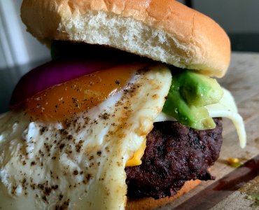 The Caveman is loaded with red onion, bacon, fried egg, avocado, Havarti and American cheeses and a slather of mustard.